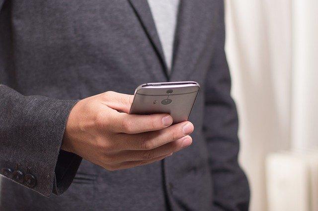 muz v obleku s telefonem